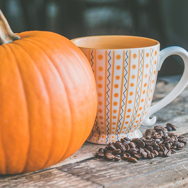 cofee cup by a pumpkin
